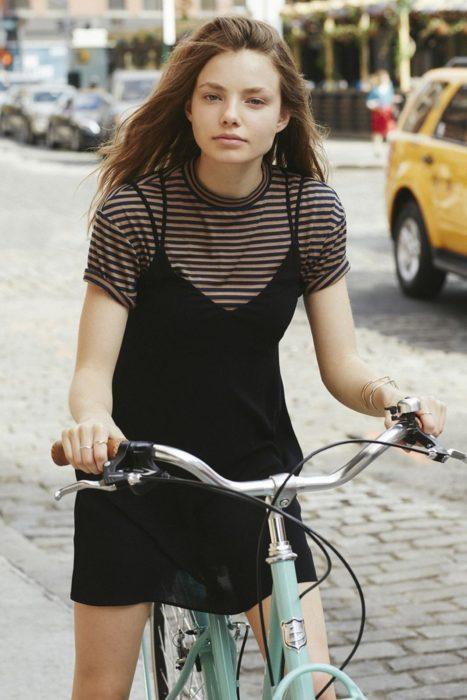 Looks de primavera; chica de cabello castaño rubio largo, sin maquillaje, andando en bicicleta con un vestido negro sin mangas sobre una camisa básica de rayas café