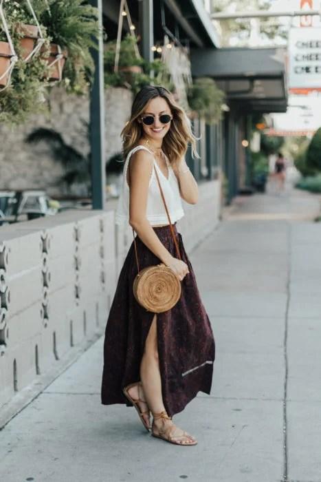 Looks de primavera; mujer con blusa de algodón blanca, falda larga color vino floreada, sandalias de piso y bolsa de mano de mimbre; cabello rubio ombré