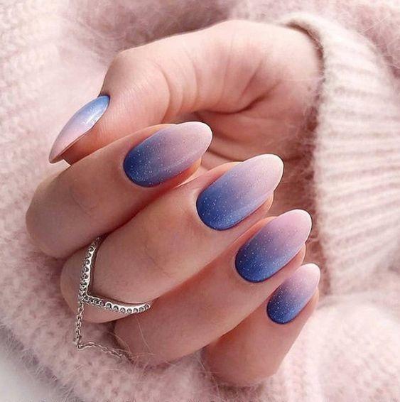 Mano de mujer con uñas ovaladas en color azul pastel