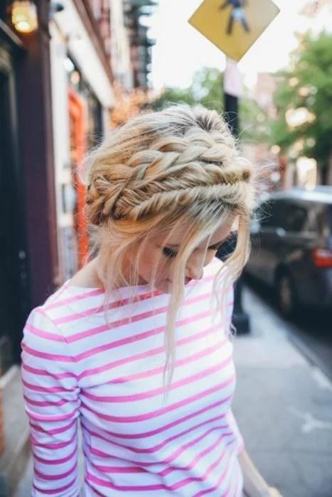 Ideas de peinados para el calor; chica rubia con blusa de rayas rosas y blancas, peinada con dos coronas de trenzas diferentes