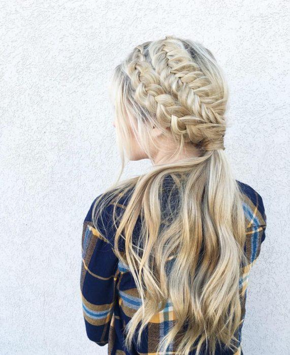Ideas de peinados para el calor; chica de cabello largo y rubio peinada con dos trenzas diferentes y una cola de caballo baja