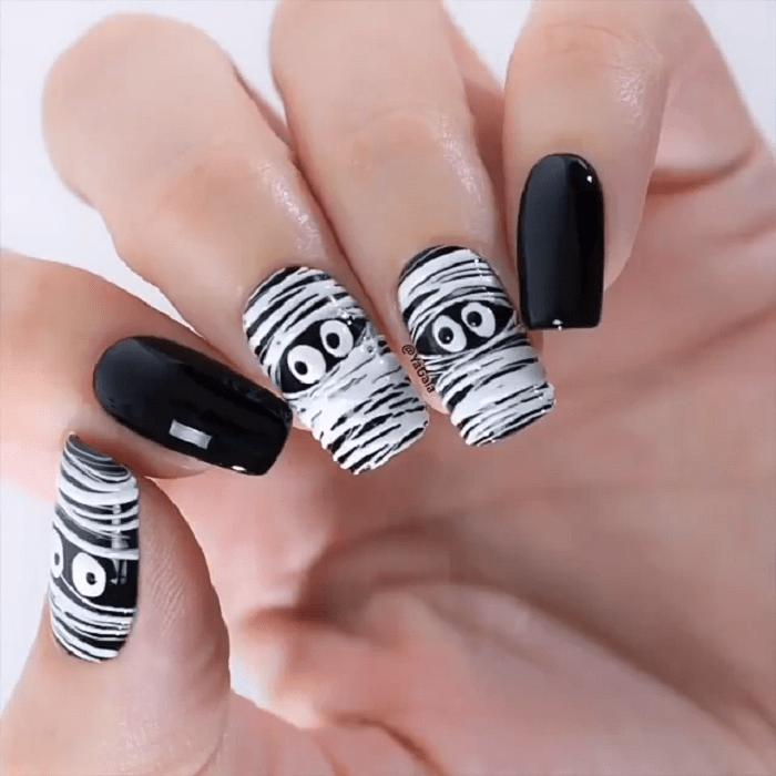 Manicura en color negro con diseño en varios dedos de momias