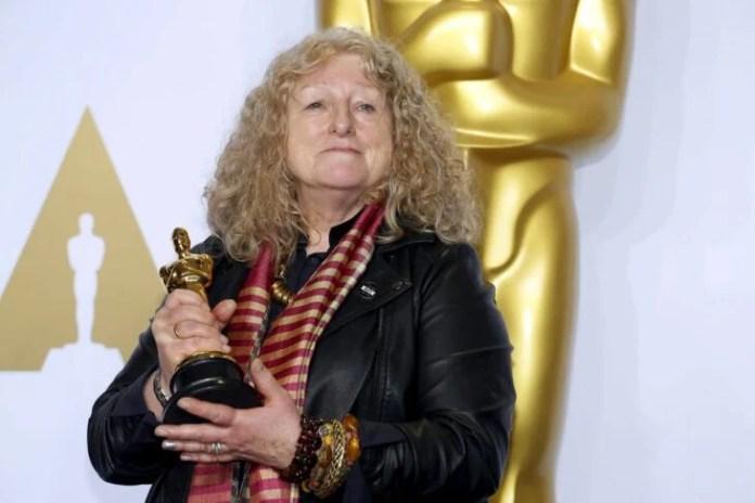 Jenny Beavan holding her Oscar statuette