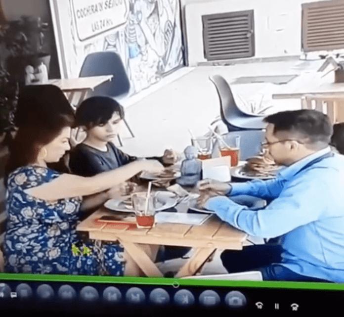 Familia poniendo cabellos en la comida de un restaurante