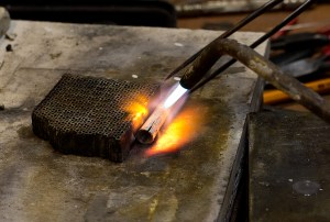 A silversmith heats a piece of silver with a blow torch