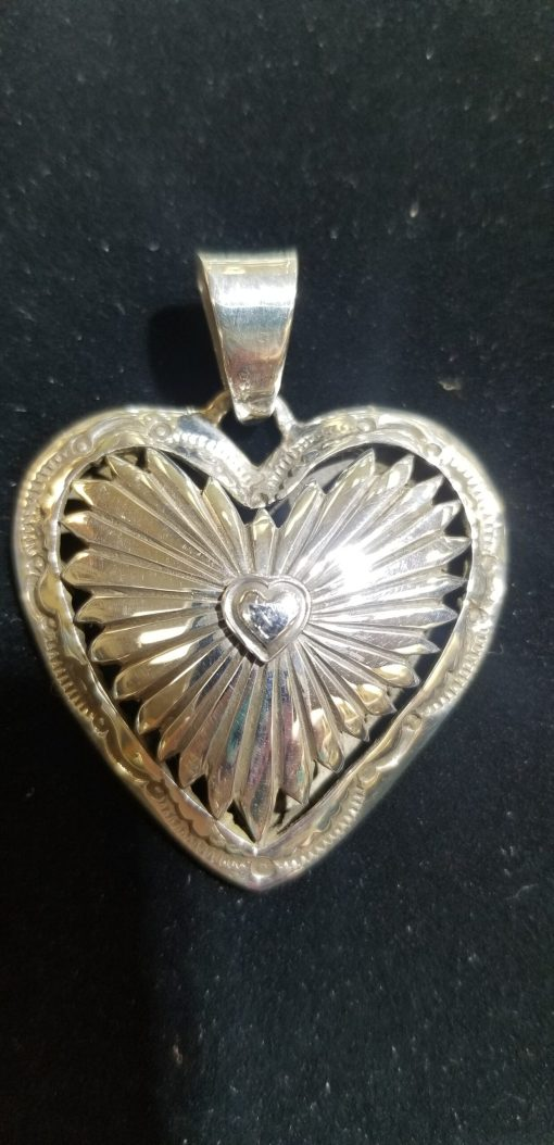 Navajo Sterling Silver Heart Pendant by DJ features Sunrise patterns and another heart in the center of the suns rays!