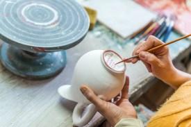 Frau bemalt Keramikvase