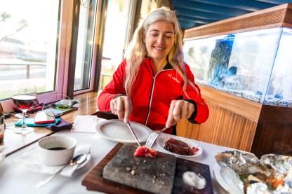 Frau brät Fisch im Restaurant Azoren