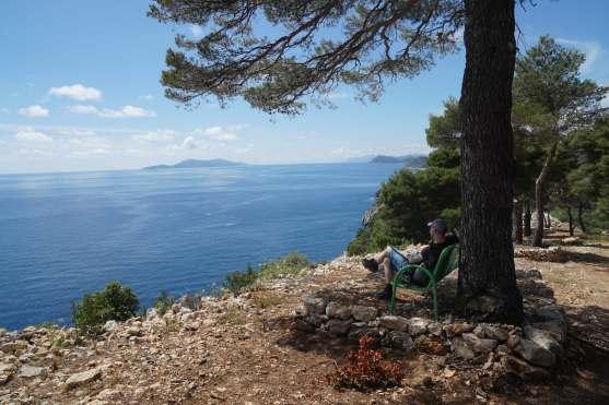 Mann auf Bank blickt auf kroatische Küste und vorgelagerte Inseln