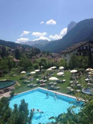 Blick auf Garten mit Liegewiese und Pool und Berge Adler Dolomiti Spa & Sport Resort