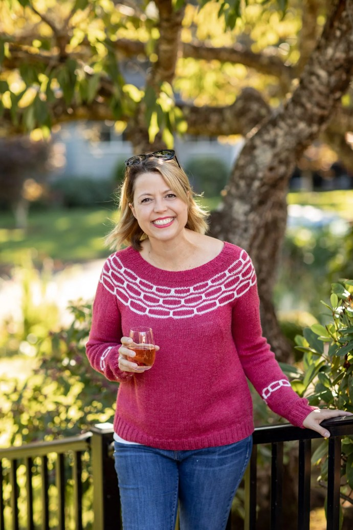 Woman in red and white sweater holding stemless wine glass