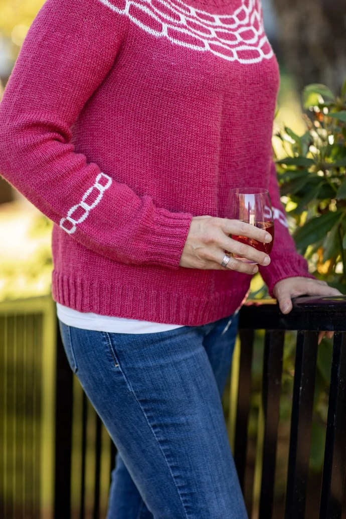 Woman's hand holding stemless wine glass