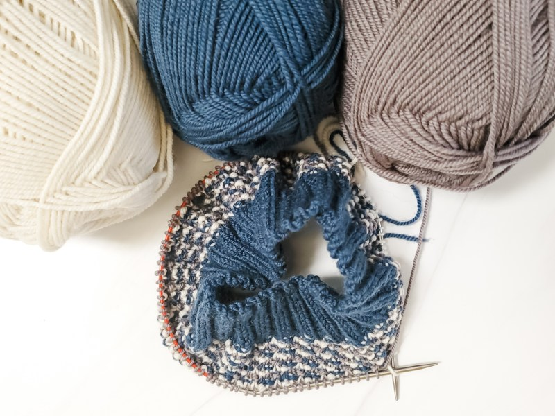 three balls of yarn attached to a small knitting project in progress