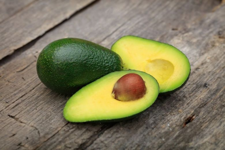 55867734 - two avocados one cut in two with seed, on wooden surface