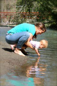 Mom holding baby over the water joyfully