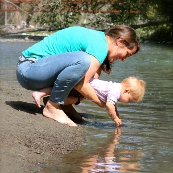 Mom holding baby over the water joyfully