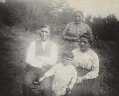 Aaron & Susan Pequongay seated, a daughter standing and a grandson in front