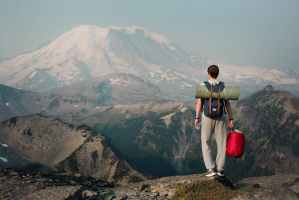 unrecognizable backpacker standing on top of mountain