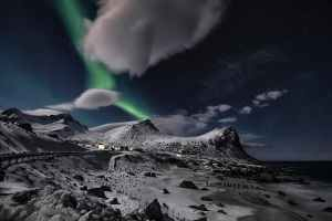 aurora borealis in starry night above snowy mountains at seaside