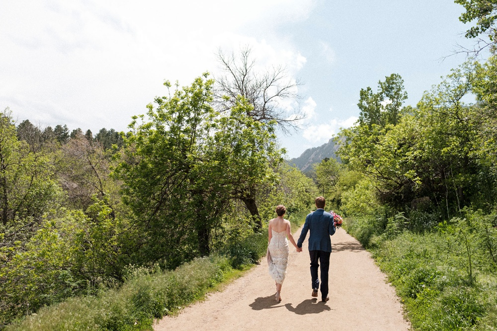 Bride and groom walking the dirt path at the base of the flatirons at Chautauqua Park in Boulder.
