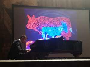 Il pianista Alberto Chawalkiewicz suona davanti all'immagine dell'opera di Lodola