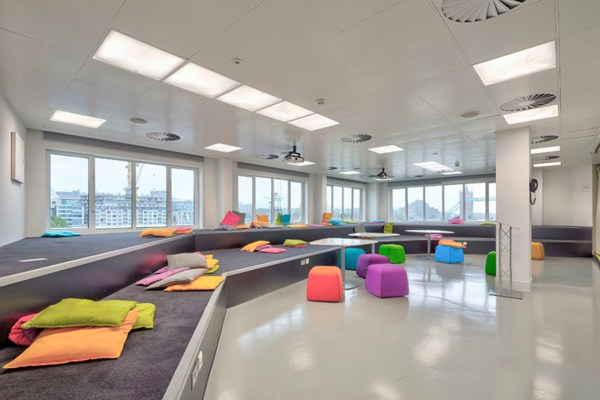 funky coloured stools around tables and floor cushions dotted about a carpeted space with views of Tower Bridge