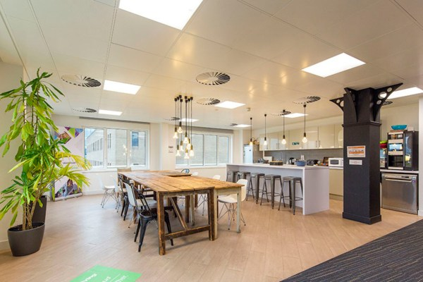 break out area with a homely feel and open plan kitchen and wooden dining style table