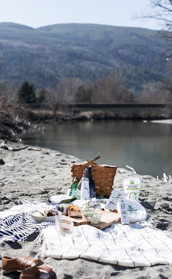 vintage wood picnic basket with compostable products for earth day at the beach