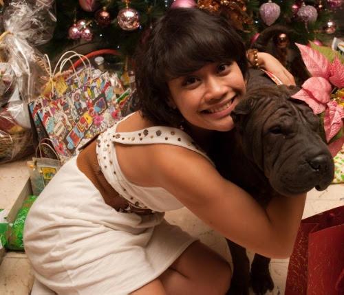 girl hugging black dog, holiday season