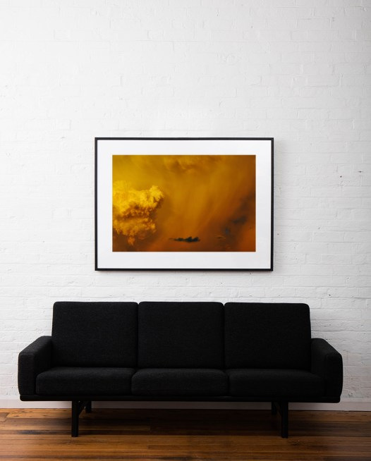 A Large horizontal photo of Australian Landscape in a Summer afternoon with orange and yellow clouds framed in black timber on white wall above sofa