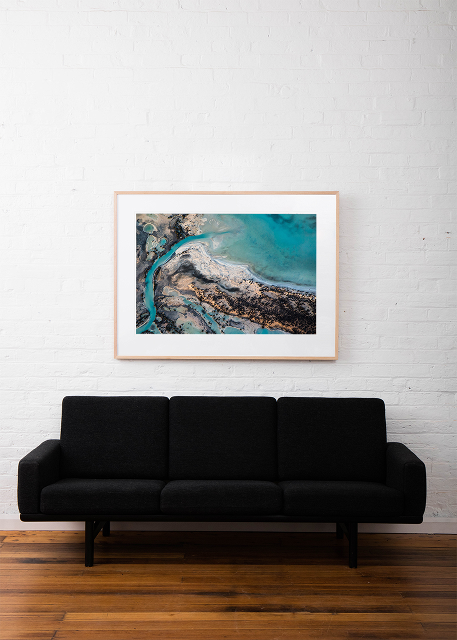 A horizontal abstract aerial photo of water taken in Australia in colour of blue, green and grey framed in raw timber on white wall above sofa