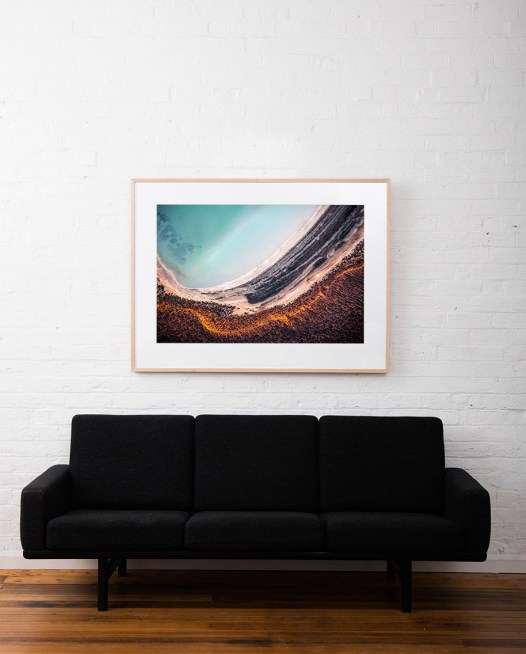 A large horizontal abstract, aerial photo of sand and water in Australian Landscape in Orange, blue and brown framed in raw timber on white wall above sofa