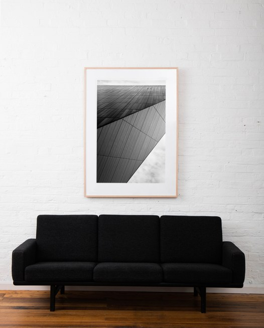 Large Vertical black and white photographic art print of buildings by Alan Moyle framed on raw timber above sofa