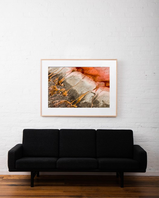 Red and gold aerial photo of the Western Australian landscape print framed in timber frame on white wall above sofa