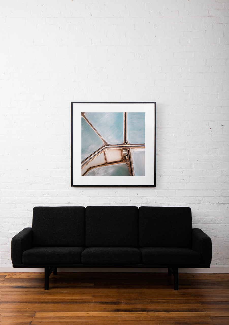 A Square abstract Aerial photo of Australian Landscape in Blue and Pink framed in rblack timber on white wall above sofa