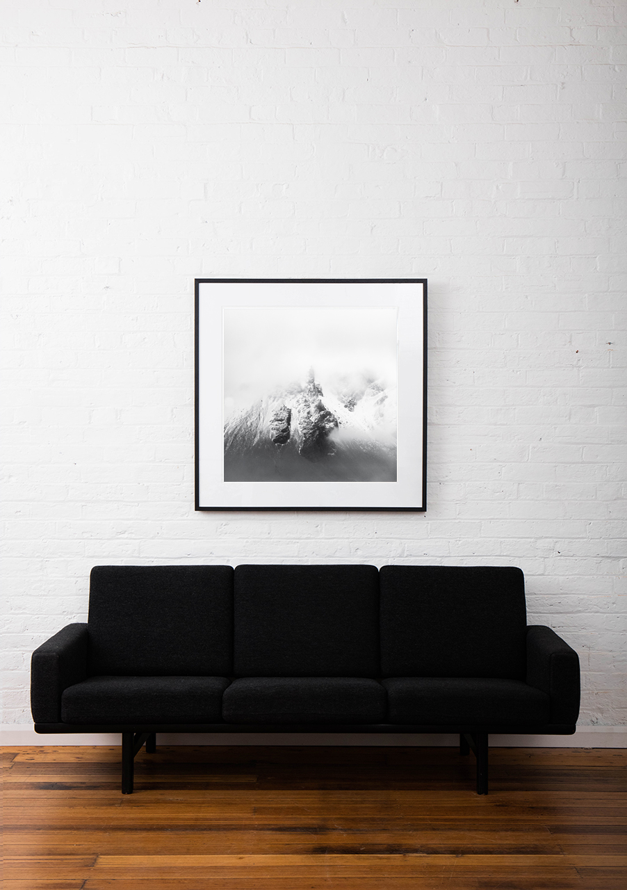 A photographic prints of icelandic mountains covered snow framed in black timber on wall above sofa