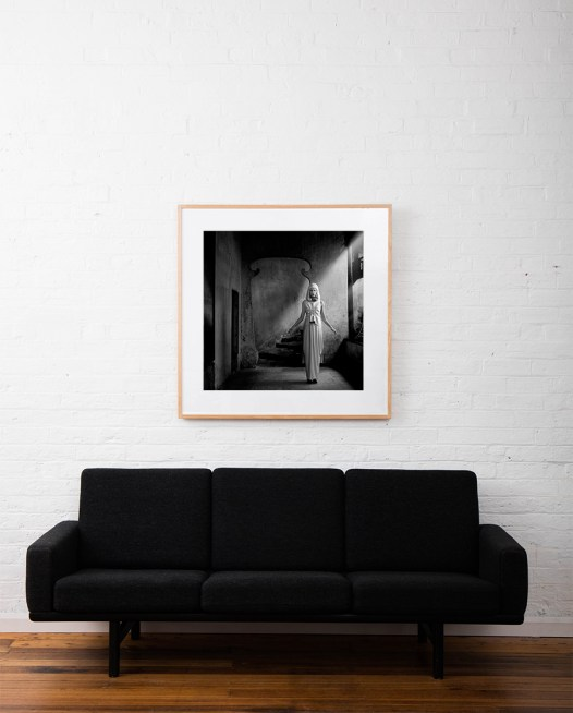 A Square Black and white photographic art print of a figure(lady) by Robert Earp framed in raw timber on wall above sofa