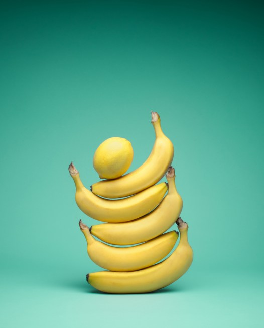 Still Life photo of a lemon on top of 5 bananas.