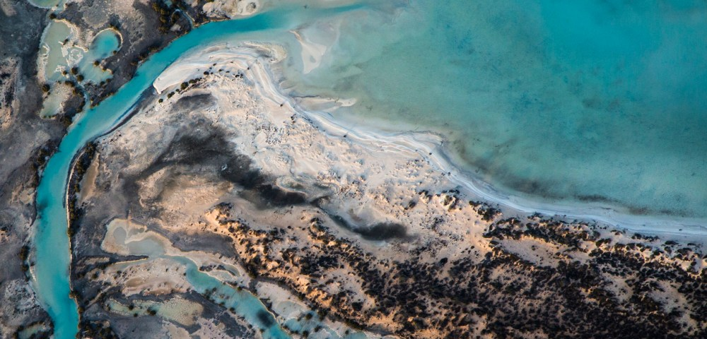 A horizontal abstract aerial photo of water taken in Australia in colour of blue, green and grey
