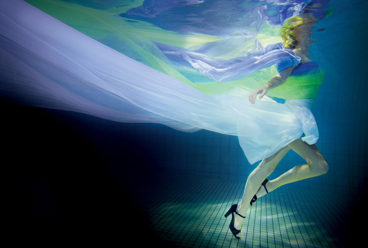 A photographic art print of a girl under water in blue, green and purple