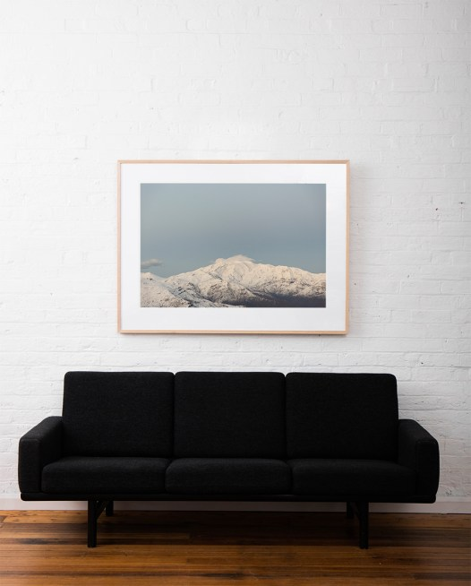 Large Photographic Landscape taken in the Andes, Chile of mountains, snow and clouds framed in raw timber above sofa