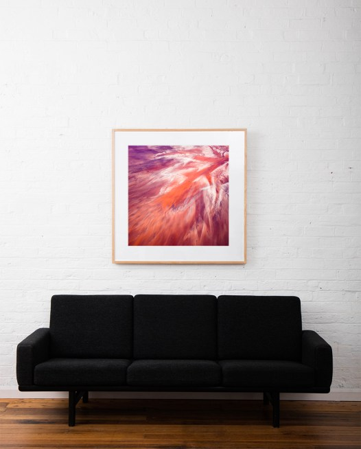 A Large Square Abstract, Aerial photo of Australia Landscape in Pink, Purple and Red framed in raw timber on white wall above sofa