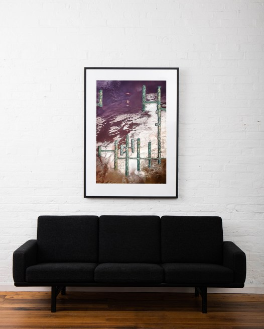 A Large Vertical Abstract Aerial photo of Australian Landscape in Pink, Purple and Red framed in black timber on white wall above sofa