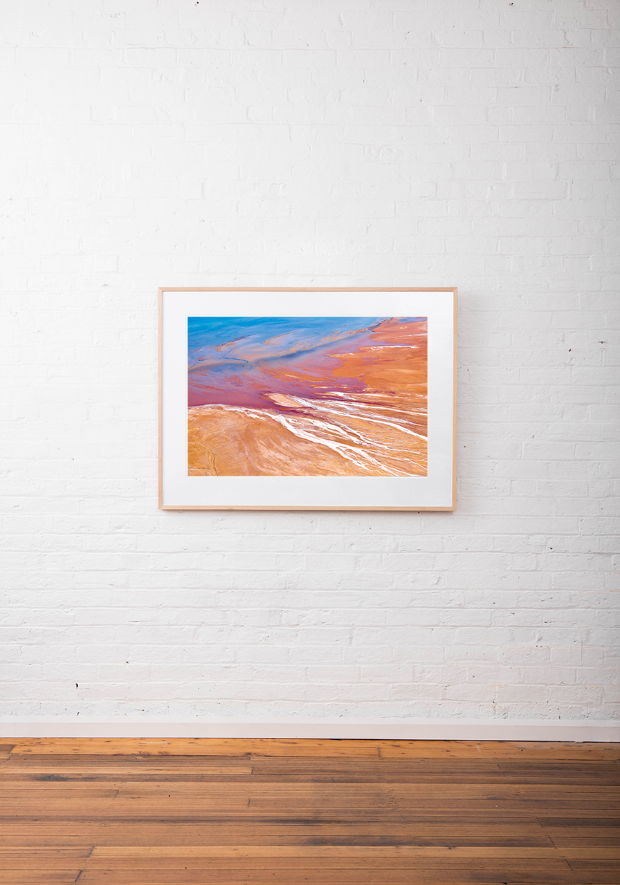 A large Abstract Aerial Landscape photo taken in Shark Bay, Australia with splash of colour in orange pink and blue framed raw timber on white wall