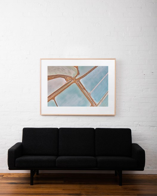 A large abstract aerial photo Water in blue and pink taken in Australia framed in raw timber on white wall above sofa