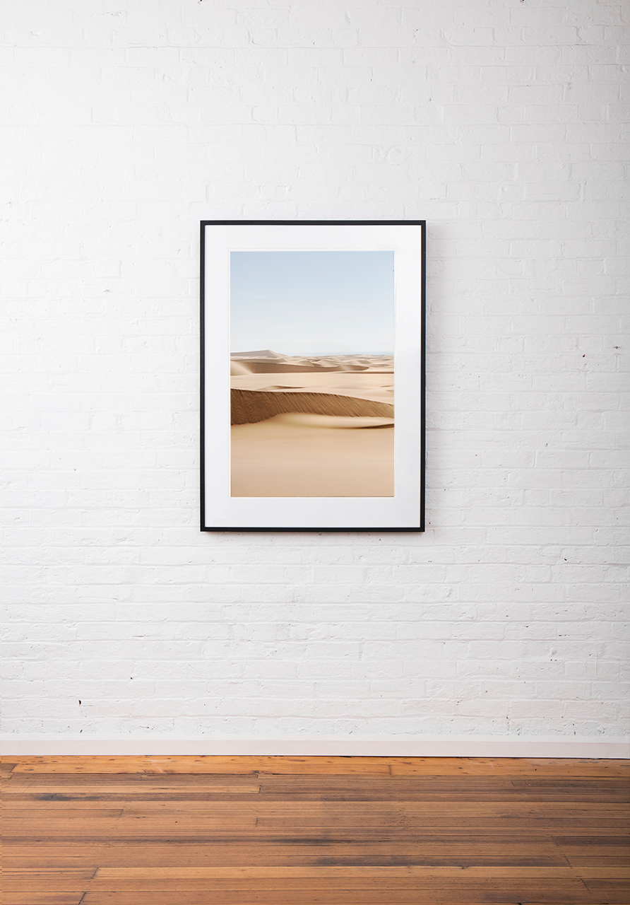 A photograph of Africa desert framed in black timber on white wall
