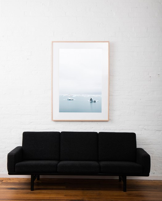 Large Print of Icelandic Landscape of glacier, snow water and sky in blue and white. Framed in raw timber on white wall above sofa