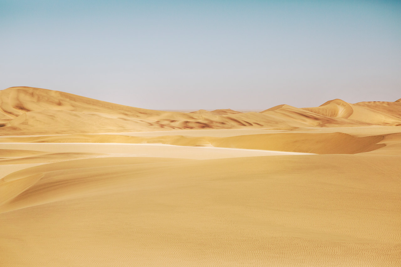 A photograph of Africa desert in yellow sand and blue sky