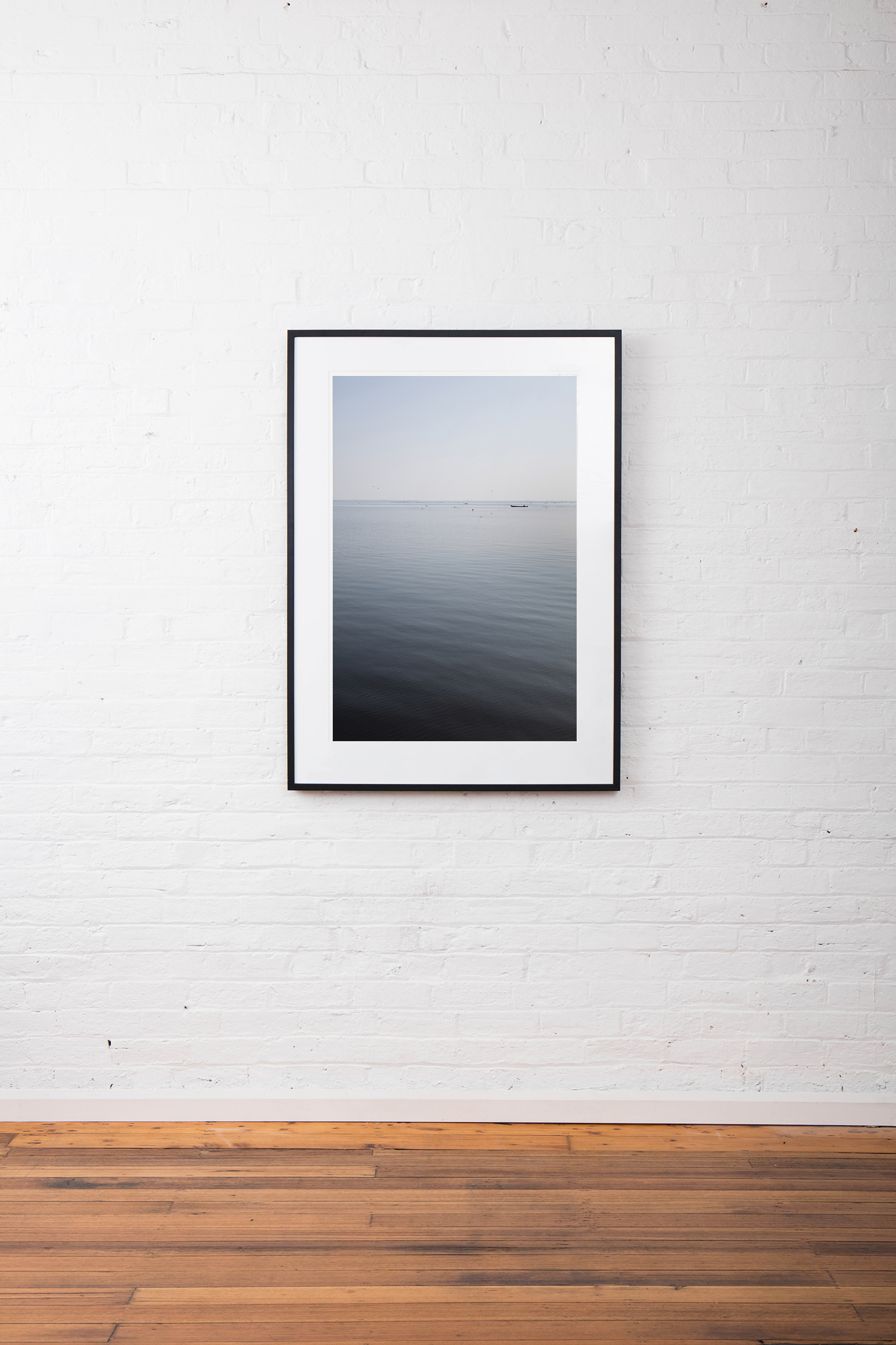A large vertical abstract image of water - blue grey, taken in India Landscape by Elizabeth Bull framed on black timber frame on white wall