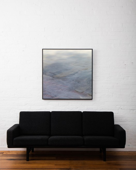 Aerial landscape photo of inland Australia in grey pink blue colours framed in black timber above sofa